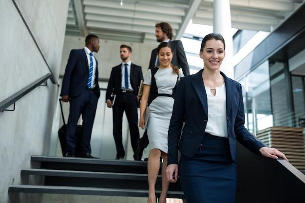 Femme d'affaires confiant avec des collègues en descendant les escaliers