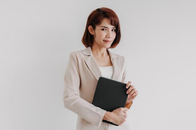 Femme d'affaires confiant tenir une tablette isolé sur fond blanc