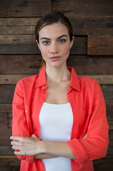 Femme d'affaires confiante debout avec les bras croisés au bureau