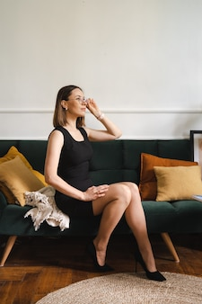 Femme d'affaires confiante portant des lunettes dans une robe classique noire assise dans un appartement moderne sur un canapé