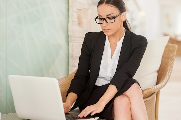 Femme d'affaires confiante et prospère. jeune femme confiante en tenues de soirée travaillant sur un ordinateur portable tout en étant assise sur une chaise confortable