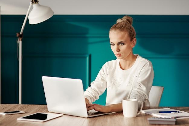 Femme d'affaires confiante en tapant sur un clavier d'ordinateur portable