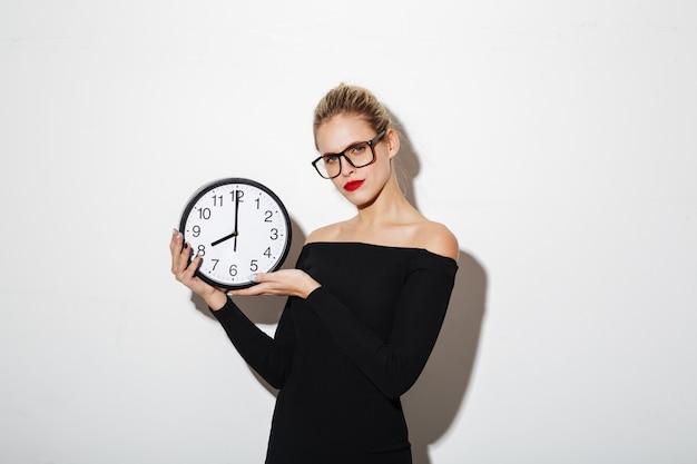 Femme d'affaires confus tenant horloge.