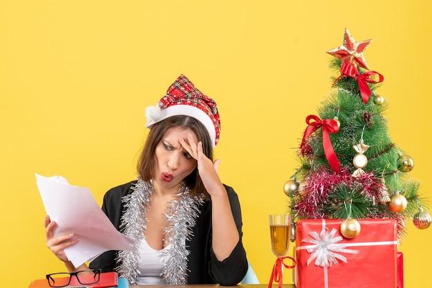 Femme d'affaires confuse en costume avec chapeau de père noël et décorations de nouvel an tenant des documents et assis à une table avec un arbre de noël dessus dans le bureau