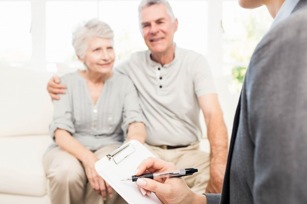 Femme affaires, conversation, couple aîné, écriture, presse-papiers, maison