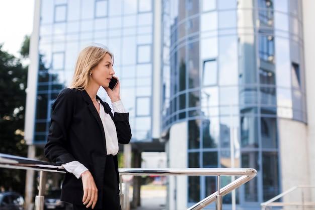 Femme affaires, conversation, téléphone, devant, bâtiment