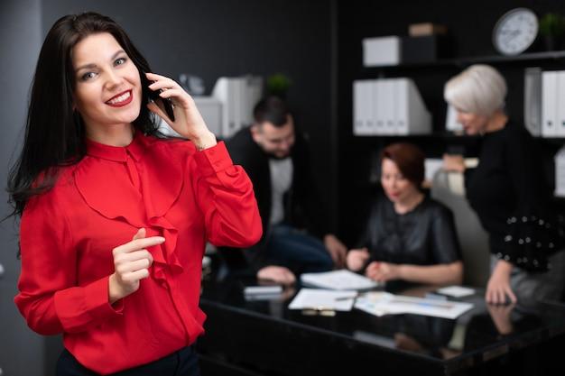 Femme affaires, conversation, téléphone, sur, employés bureau, discuter, projet