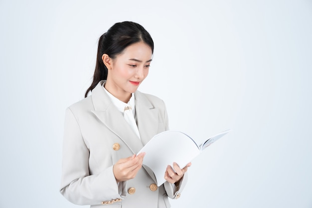Femme d'affaires en costume gris, lecture de document et préparation de la réunion.