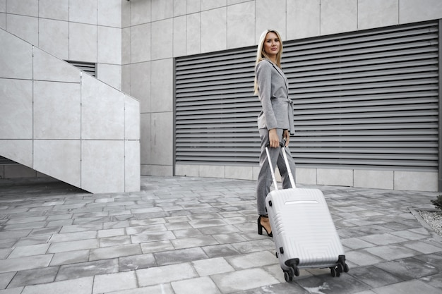 Femme d'affaires en costume gris en voyage d'affaires marchant avec ses bagages dans la ville
