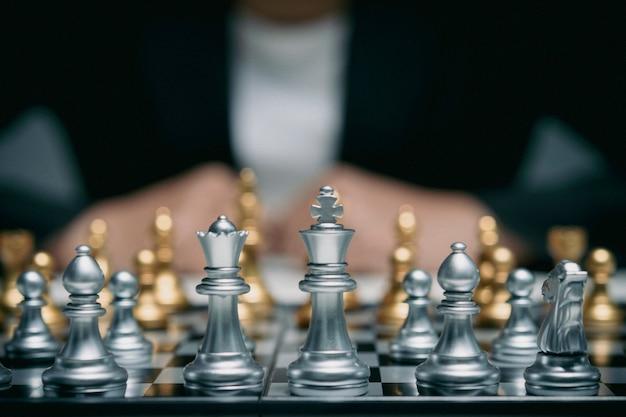 Femme d'affaires en costume joue aux échecs. gros plan d'une main féminine sur un concept d'entreprise de compétition de jeu d'échecs sur pion, mise au point sélective sur les pièces d'échecs, concept d'entreprise d'échecs, leader et succès.