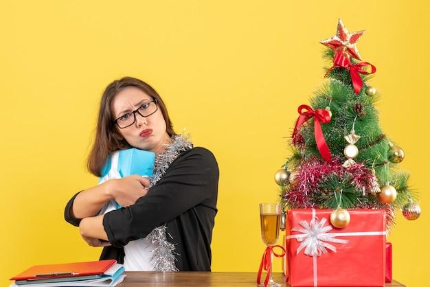 Femme d'affaires en costume avec des lunettes cachant son cadeau de façon surprenante et assis à une table avec un arbre de noël dessus dans le bureau