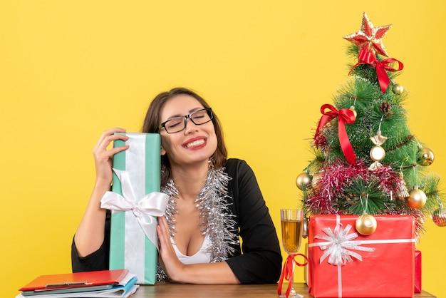 Femme d'affaires en costume avec des lunettes montrant son cadeau rêvant de quelque chose et assis à une table avec un arbre de noël dessus dans le bureau