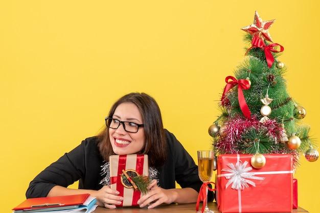 Femme d'affaires en costume avec des lunettes tenant son cadeau et assis à une table avec un arbre de noël dessus dans le bureau