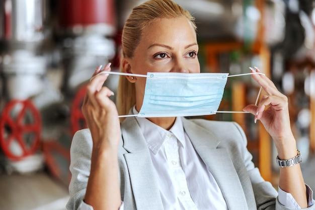 Femme d'affaires en costume mettant un masque facial en se tenant debout dans son usine pendant le coronavirus.