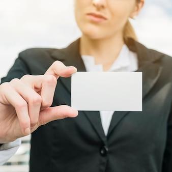 Femme d'affaires en costume montrant une carte de visite blanche vierge
