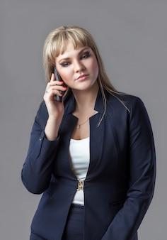 Femme d'affaires en costume parlant sur un téléphone portable.
