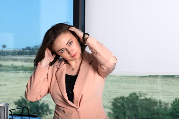 Femme d'affaires en costume rose joue avec ses cheveux bruns, ajuste la coiffure