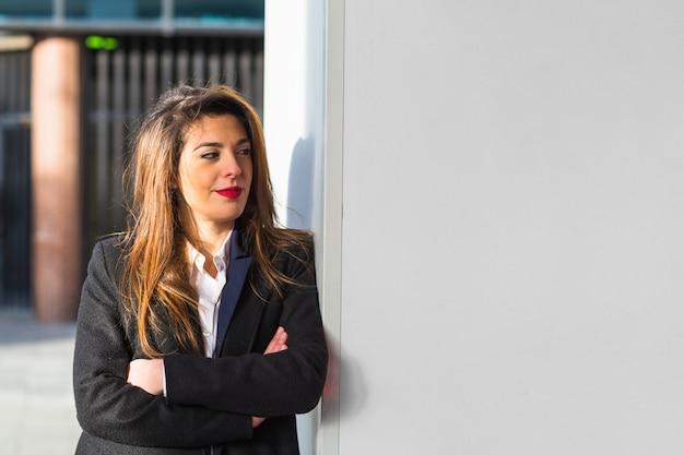 Femme d'affaires en costume se penchant sur le mur