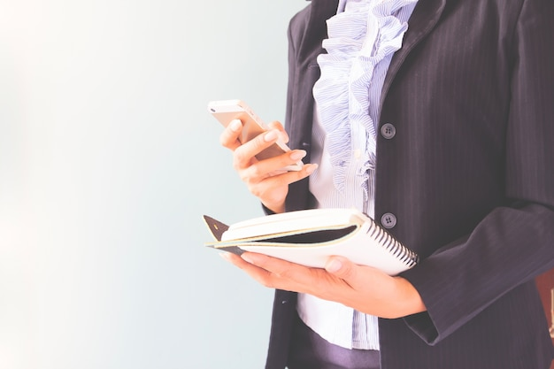 Femme d'affaires en costume sombre tenant téléphone mobile et cahier, concept d'entreprise avec copie espace