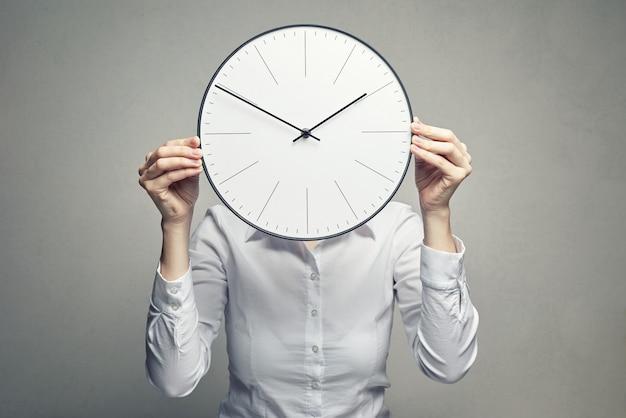 Femme d'affaires couvrant son visage avec une horloge