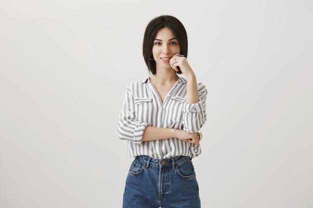 Femme d'affaires créative intriguée souriant, pensant ou faisant un choix