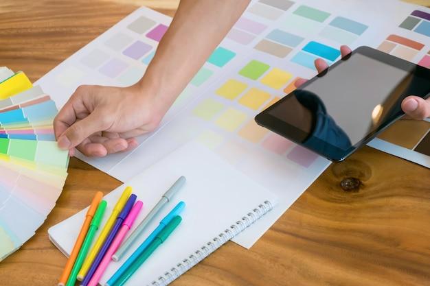 Femme d'affaires créative utilisant une tablette et travaille sur des tableaux de couleurs sur le bureau d'un bureau moderne