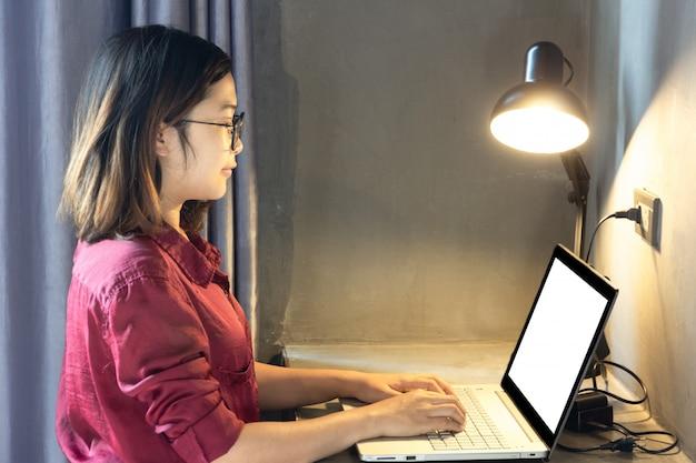 Femme affaires, dactylographie, ordinateur portable, à, blanc, écran blanc, pour, maquette, modèle, fond, à, lampe