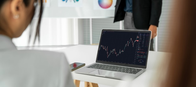 Femme d'affaires dans l'analyse des données boursières à l'aide d'un ordinateur portable avec compétence