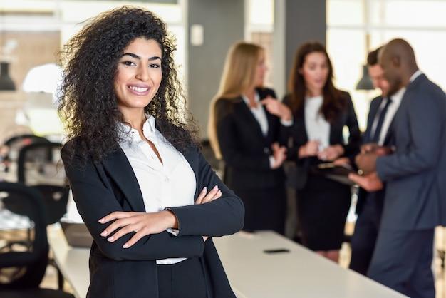 Femme d'affaires dans un bureau moderne avec des hommes d'affaires travaillant