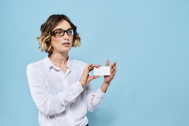 Femme d'affaires dans une chemise blanche et des lunettes posant en studio, fond clair