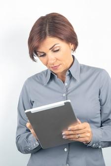 Femme d'affaires dans une chemise et une tablette dans ses mains