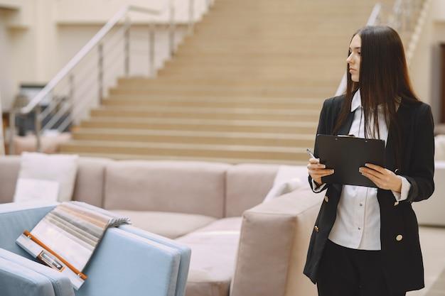 Femme d'affaires dans un costume noir au bureau