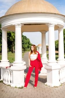 Femme d'affaires dans un costume rouge près d'un gazebo blanc