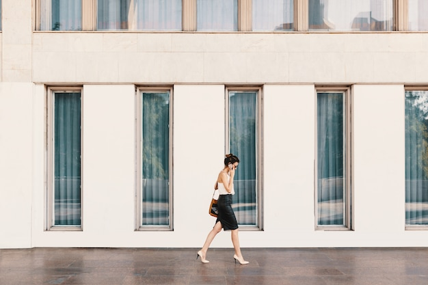 Femme affaires, dans, jupe cuir, conversation téléphone