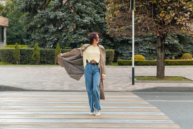 Femme d'affaires dans un long imperméable traversant la route dans la rue par temps ensoleillé