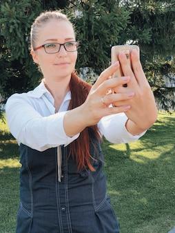 Femme d'affaires dans le parc avec smartphone à l'heure du déjeuner