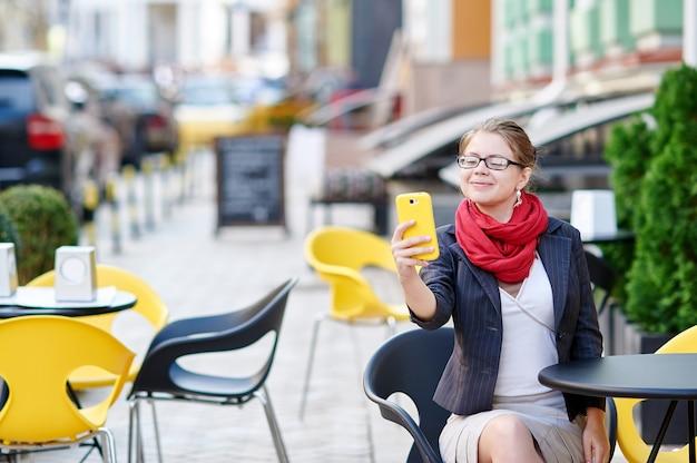 Femme d'affaires dans des verres assis à une table dans un café et rend selfie