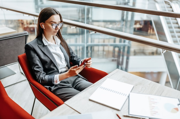 Femme d'affaires dans des verres sur le lieu de travail utilise le téléphone et s'assoit à la table. manager au bureau.