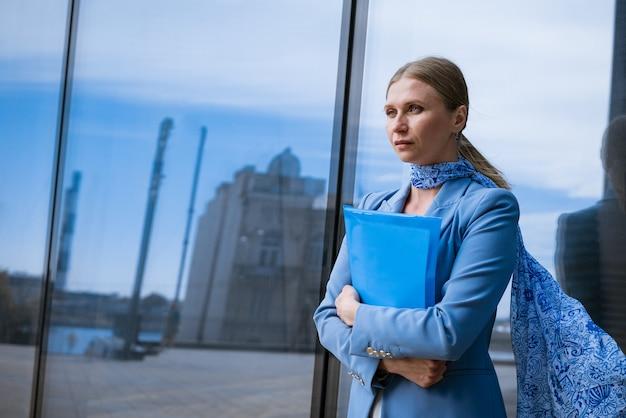 Une femme d'affaires dans une veste bleue tient un dossier avec des papiers à la main devant un concept d'immeuble de bureaux en verre de femmes qui réussissent