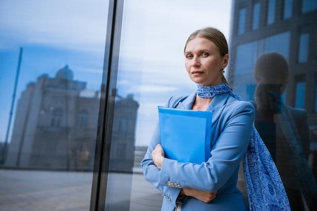 Une femme d'affaires dans une veste bleue tient un dossier avec des papiers à la main devant un immeuble de bureaux en verre