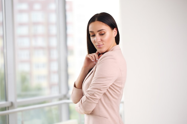 Femme d'affaires dans une veste rose et un bureau lumineux par les fenêtres