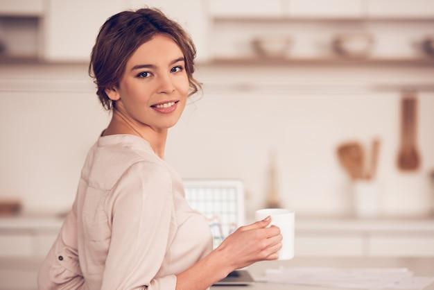 Femme d'affaires dans des vêtements décontractés tient une tasse