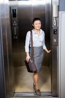 Femme affaires, debout, ascenseur, bureau
