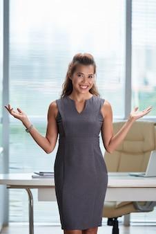 Femme affaires, debout, bureau, mains écartées, smie, visage