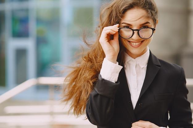 Femme affaires, debout, dehors, ville, bureau, bâtiment