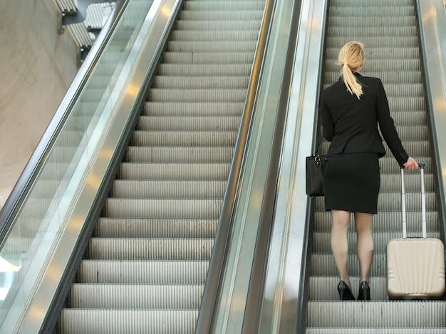 Femme d'affaires debout sur l'escalator avec des sacs de voyage