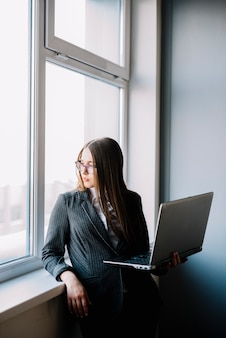 Femme d'affaires debout à la fenêtre avec un ordinateur portable