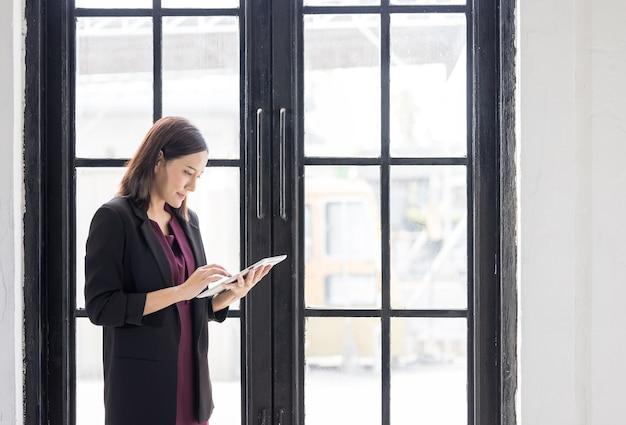 Femme d'affaires debout près d'une fenêtre à l'aide d'un ordinateur portable au bureau