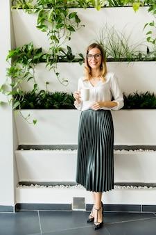 Femme d'affaires debout à son bureau par des plantes vertes et boire du thé