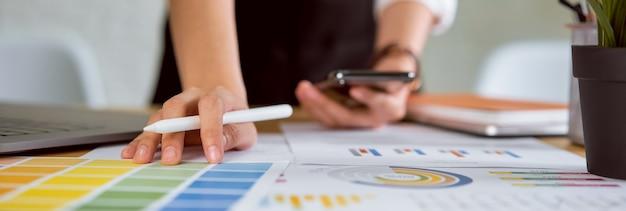 Femme d'affaires debout et tenant un stylo numérique, smartphone avec travail sur ordinateur portable au bureau.